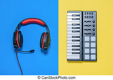 Headphones with microphone and wires and music mixer on yellow and blue background. The view from the top.