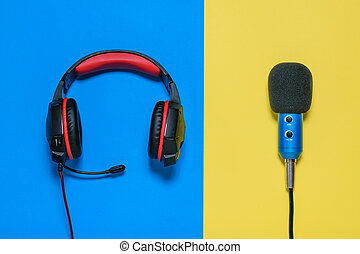 Headphones with microphone on yellow and blue background. The view from the top.