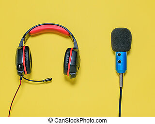 Headphones with microphone on yellow background. The view from the top.