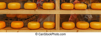 Heads of cheese in store window.