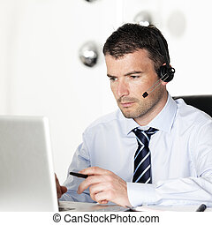 headset and laptop - man in office with laptop and headset...