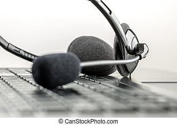 Monochrome black and white image of a headset lying on a laptop computer keyboard conceptual of telemarketing, call center, client services or online support.