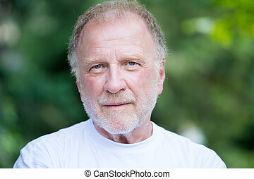 Closeup headshot portrait of happy, confident, cheerful, smiling senior mature man, isolated green trees foliage background. Positive human emotions, facial expressions, feelings, attitude