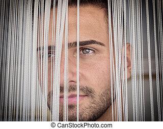 headshot, de, bonito, homem jovem, atrás de, cadeias, cortina