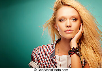 Headshot of a young stylish blonde in a plaid shirt
