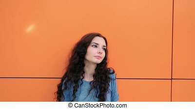 Headshot of confident pretty young woman, on orange wall...
