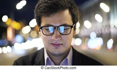 Headshot of handsome young businessman in glasses web surfing with phone, night