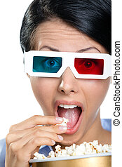 Headshot of the spectator in 3D glasses eating popcorn -...
