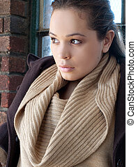 headshot of woman wearing sweater and coat outdoors