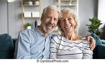 Headshot portrait happy cheerful 60s couple hugging sitting ...