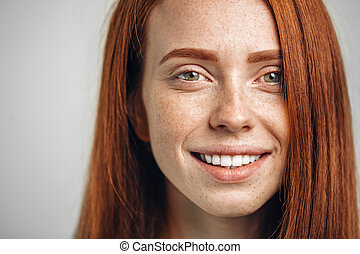 headshot portrait of happy ginger girl with freckles smiling