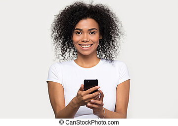 Headshot portrait smiling african woman holding smartphone looking at camera