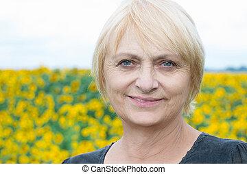 Headshot portrait, smiling aged blond woman, direct look, light eyes
