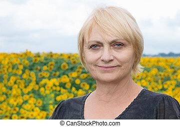Headshot portrait, smiling aged white woman, direct look, light eyes