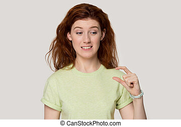 Head shot studio portrait confused red-headed girl looking at hand showing with fingers something small feels perplexed about tiny size insufficient length or thickness pose on grey wall concept image.