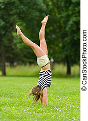 Young girl doing headstand at the park with narrow depth of field
