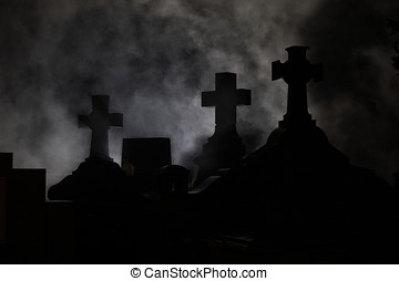 Headstone cross in Graveyard at night.