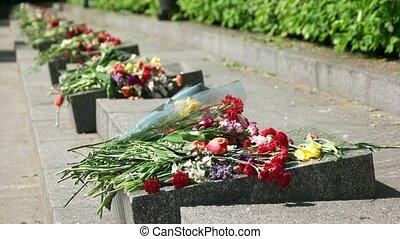 Headstone memorials with flowers bouquets. Granite stones, outdoor.