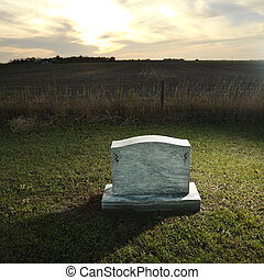 Headstone marking grave in rural countryside at sunset.