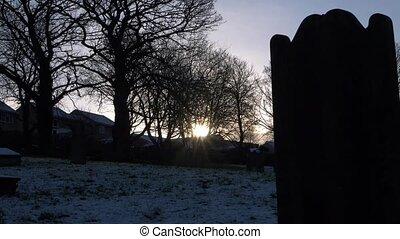 Headstone silhouette in graveyard against dusk sunset medium panning shot
