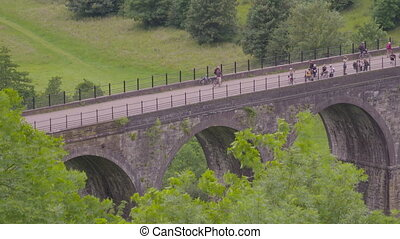 Medium high angle still shot of tourists and hikers along the famous Headstone Viaduct, Monsal Trail in Peak District, UK