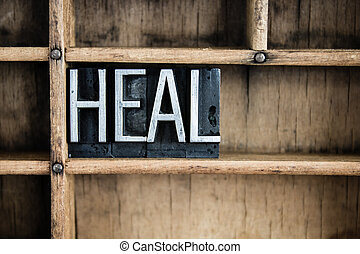 "The word ""HEAL"" written in vintage metal letterpress type in a wooden drawer with dividers."