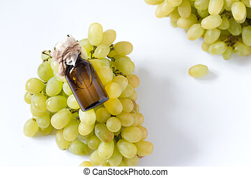 Healing grapes seeds oil in a glass jar, fresh grapes on white background, seed extract has antioxidant and nourishing the skin, spa concept, selective focus macro front view. Bio, eco products. .