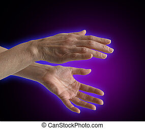 Healer's outstretched hands sensing energy on a black and purple background