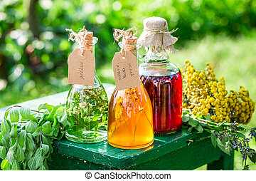 Healing herbs in bottles as homemade cure in garden
