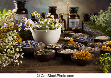 Healing herbs on wooden table, mortar and herbal medicine -...