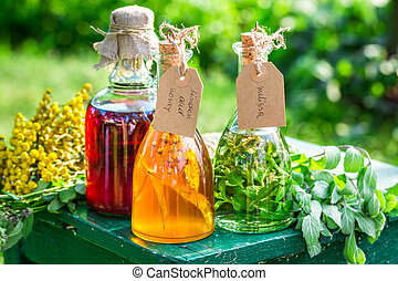 Healing tincture in bottles with herbs and alcohol