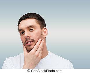 beautiful calm man touching his face
