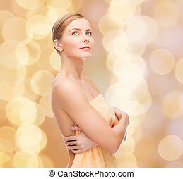 health and beauty concept - beautiful woman in towel looking up