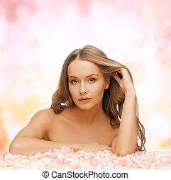 woman with long hair and rose petals