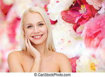 smiling young woman touching her face skin