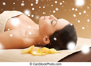 woman in spa salon lying on the massage desk - health and...
