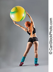 Health and Fitness woman in gym outfit with a Pilates ball