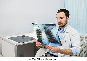 Health and mood. Serious Doctor talking to patient keeps chest X-ray in hands while sitting at a table the hospital.