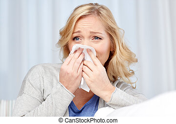 ill woman blowing nose to paper napkin