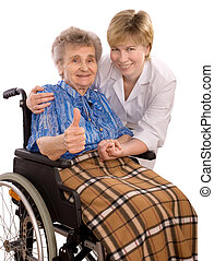 Health care worker and elderly woman in wheelchair giving the thumbs-up sign