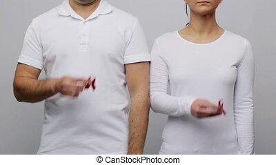man and woman in t-shirt with red awareness ribbon - health,...