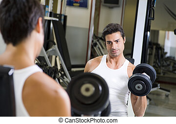 health club: guy in a gym doing weight lifting at the mirror...
