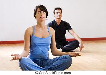 health club: man and women doing yoga.