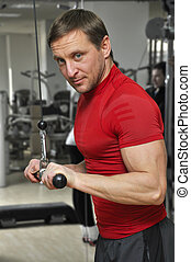 man in a gym - health club: man in a gym doing weight...