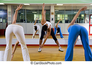 health club: women doing stretching and aerobics