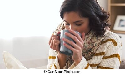 sick young woman in scarf drinking hot tea at home - health,...