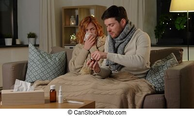 sick young couple at home in evening - health, flu and ...