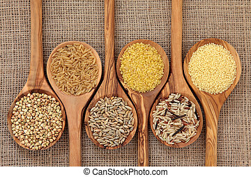 Cereal and grain selection of bulgur wheat, buckwheat, couscous, rye grain and brown and wild rice in olive wood spoons on hessian sacking background.