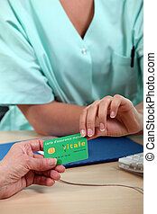 health insurance card being passed from patient to medical...