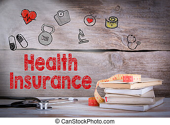 Health Insurance Concept. Stack of books and a stethoscope on a wooden background